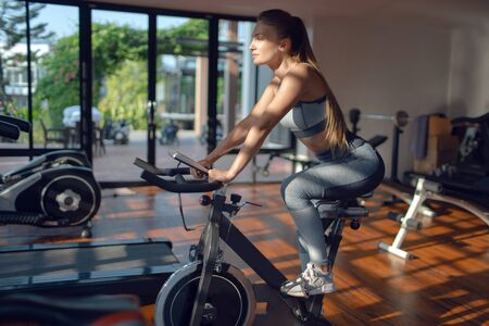 Young beautiful girl on an exercise bike in a gym