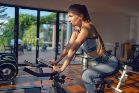 Young beautiful girl on an exercise bike in a gym. Cycling Stok Fotoğraf