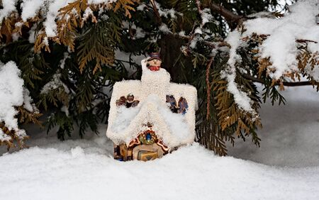 The toy lodge of snowmen costs in a snowdrift, lit with the sun.
