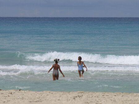girls on beautyful paradise beach swimming