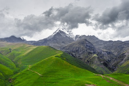 stratovolcano: Trekking in Caucasus Mountains (Georgia) - view of the Mount Kazbek covered with clouds