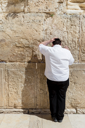 western wall: JERUSALEM, ISRAEL - MARCH 15, 2016: Man praying at the mens section of the Wailing (Western) Wall in the old town Jerusalem (Israel) Editorial