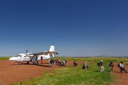 maasai mara: MAASAI MARA, KENYA - JUNE 24, 2015: Safalink plane has landed at the Maasai Mara field airport (Kenya) and its passengers are leaving the aircraft