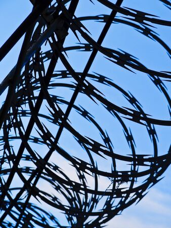concertina: Razor wire against cloudy sky