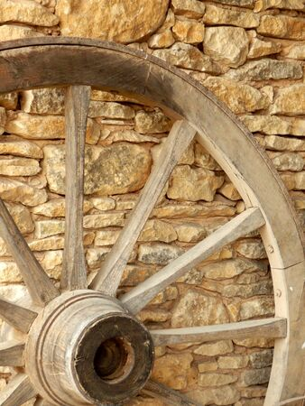 spoke: Vintage cart wheel against a stone wall Stock Photo