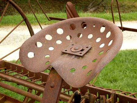 tine: Close up of a rusty metal seat on a vintage spring tine harrow