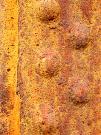 Close up of rusted riveted sheets of metal photo