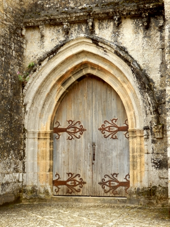 Medieval arched double doors, located at Chateau de Beynac et Cazenac, Dordogne, France photo