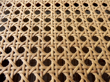 cane chair: Close up of the pattern formed by open weave rattan cane on a chair seat