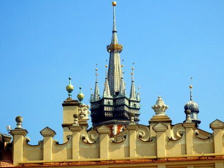 The two towers of Saint Marys Basilica as seen behind the parapet of Cloth Hall in Main Square, Krakow, Poland