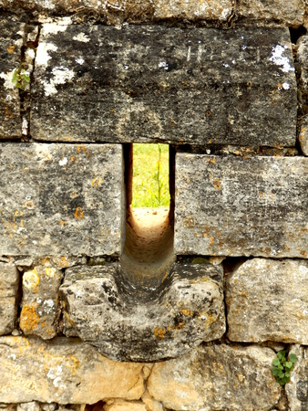 slit: Arrow slit aka arrow loop, in a fortified medieval wall of a French Chateau