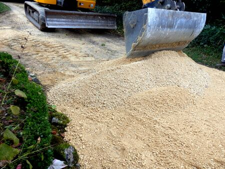castings: Old drive being covered with new castings sand and gravel Stock Photo