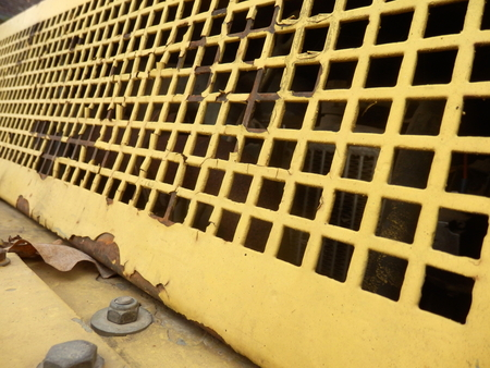compactor: Rusted grill with peeling paint, fitted to a road compactor