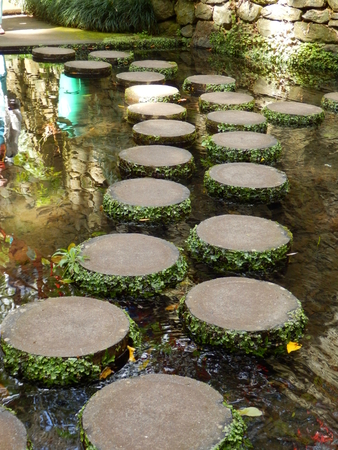 stepping: Circular stepping stones creating a beautiful curved pathway across water Stock Photo