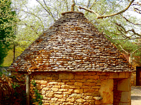 French round limestone lodge constructed of dry-stone walls and a stone tiled (lauze) roof