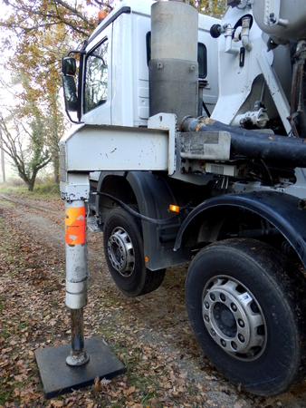 Cement lorry with stabilisers down and wheels up to provide a level work platform