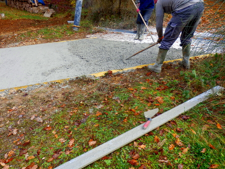 Workers levelling off freshly poured cement in the construction of a concrete driveway Reklamní fotografie