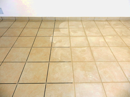 Newly laid beige floor tiles and plinths with beige grouting being applied Banco de Imagens