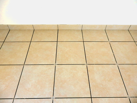 Newly laid beige floor tiles and plinths with spacers inserted to form a uniform gap Reklamní fotografie