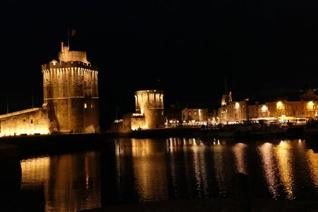 La Rochelle old port (Vieux Port) lit up at night, showing Tour Saint-Nicholas (on the left) and Tour de la Chaine (on the right) guarding the entrance to the harbour