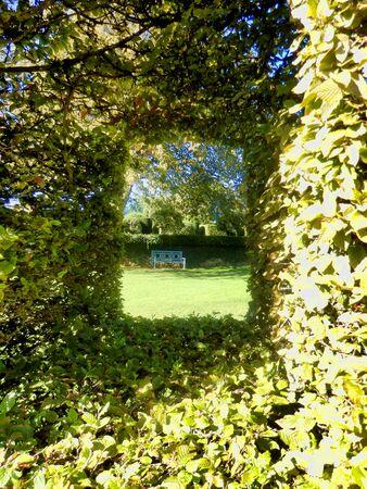 Park bench seen through a Box topiary cut out window found in Eyrignac Manor Garden, Dordogne, France