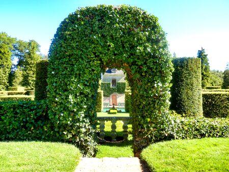 House seen through a topiary arch of Virginia Creeper found in Eyrignac Manor Garden, Dordogne, France