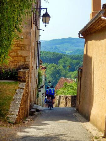 French cycling club descending the steep streets of Limeuil in Dordogne, France