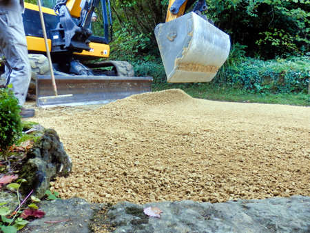 Old drive being covered with new castings (sand and gravel)