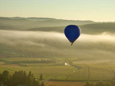 Hot air balloon floating over the mist covered Dordogne landscape at sunrise Stock Photo