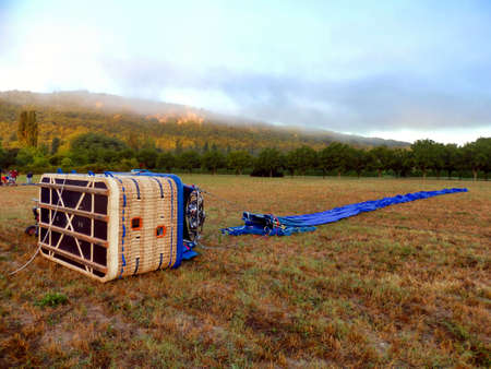 Hot air balloon laid out in a field, ready for inflating