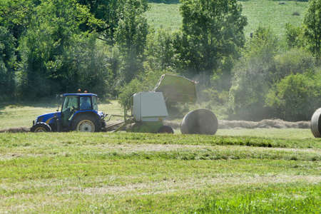 Baler opening to release a large round compacted hay bale Stock Photo