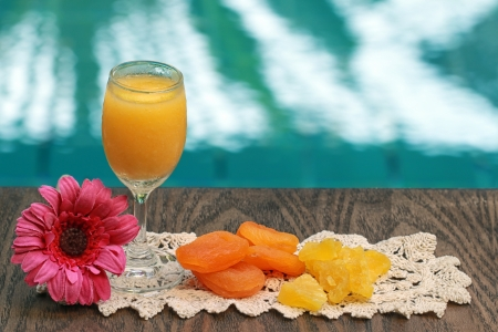 Fresh fruit juices decorated with flowers and dried fruits  Фото со стока