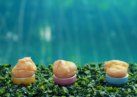scrumptious: Cream puffs with cup on green grass