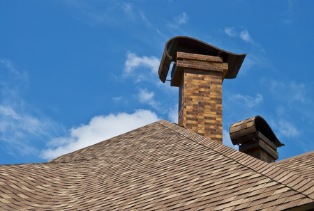 pitched: The roof of the house with two chimneys in the new design against the blue sky with clouds.