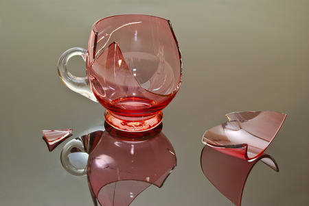 fragments: Cracked cup pink on a reflective background with chipped fragments lying around. Stock Photo