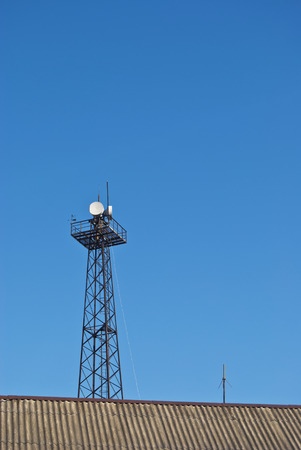 asymmetry: Tower with antennas of cellular communication, towering over the roof of the house against the clear blue sky. There is plenty of space for text. Asymmetry indices composition. Stock Photo