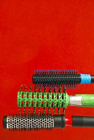 perming: Round brush massage - combs, Termobrashing, skeletal hairbrush on a red background with free space for text.