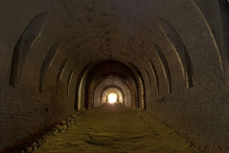 loopholes: The vaulted underground tunnel to the side of an ancient fort defensive loopholes.