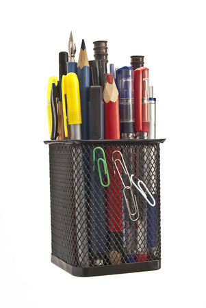 tight filled: Black, metal cup for pens and pencils in fishnet tight execution filled with stationery. Stock Photo