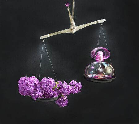 outweighs: Natural branch of lilac in the balance outweighs the bowl with a bottle of perfume.