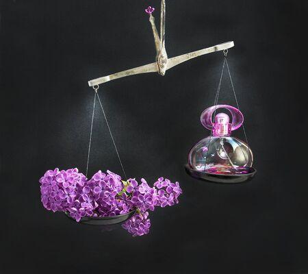 outweighs: Natural rama de lilas en la balanza pesa m�s que el recipiente con una botella de perfume. Foto de archivo
