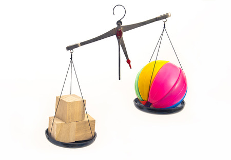 health symbols metaphors: On the scales are weighted symbolically natural and plastic toys. Superiority in the natural.