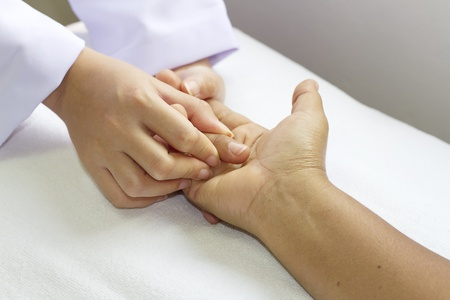 physical therapist checks range of motion for finger and hand  photo