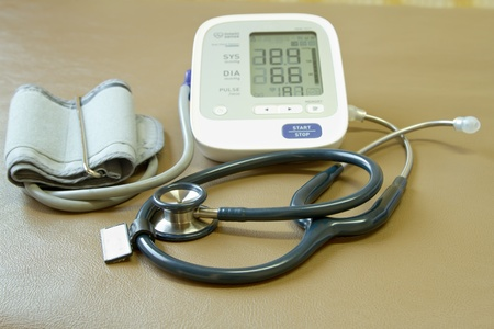 Digital blood pressure meter and stethoscope rest on the bed photo