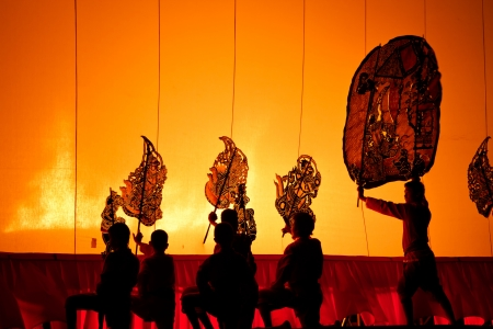 RATCHBURI, THAILAND - APRIL 14: Large Shadow Play is performed at Wat Khanon on April 14, 2012. The ancient performing art involves manipulating puppets of cowhide in front of a backlit white screen
