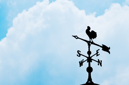 Weather vane silhouetted against a  blue sky photo