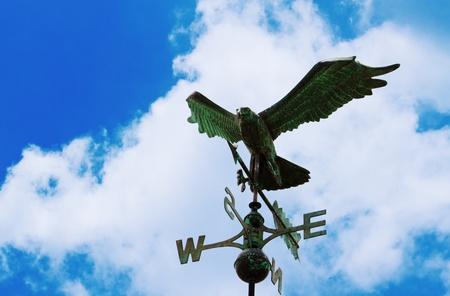 puntos cardinales: Águila veleta en el tejado en el cielo azul Foto de archivo