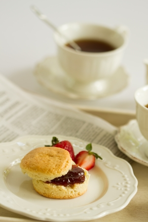 scone with strawberry jam and clotted cream , afternoon tea break , cream tea , tea party , buttermilk biscuits with newspaper photo