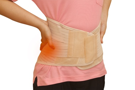 carpol:  Woman in pain from back injury wearing lumbar brace corset on  isolated background