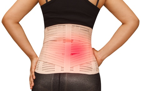 Woman in pain from back injury wearing lumbar brace corset on  isolated background
